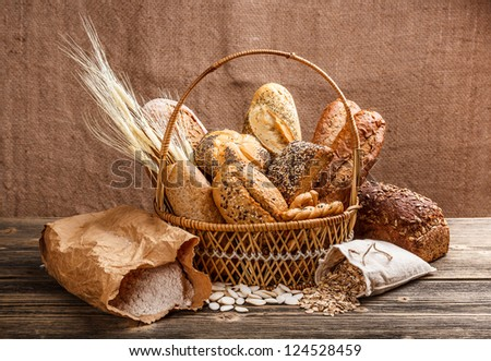 Fresh bread in the basket on wooden background - stock photo