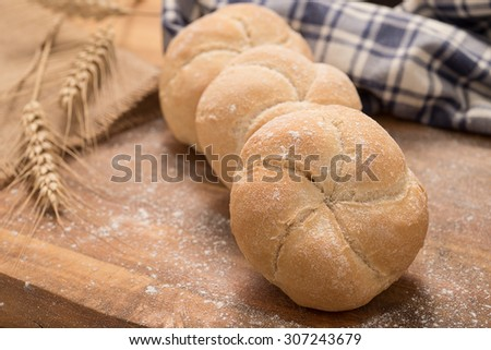 Fresh bread on a wooden board with a blue and withe checkered tablecloth