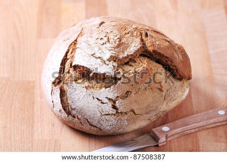 Fresh bread on a wooden cutting board with a knife