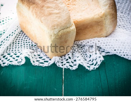 Fresh bread on wooden table - stock photo
