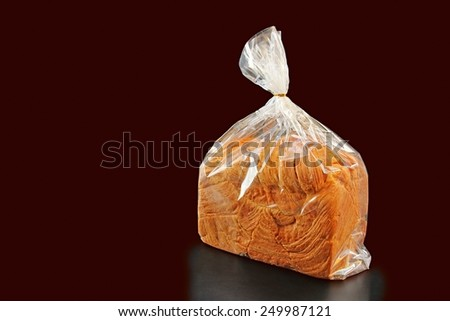Fresh bread packaged in edible plastic bag on white background. - stock photo
