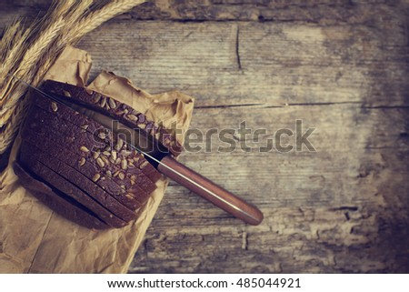 Fresh bread slice and cutting knife on rustic table