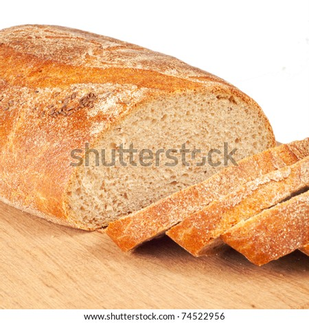 Fresh bread sliced on a wooden chopping board isolated on white - stock photo