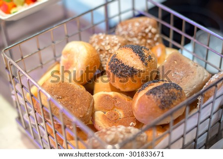Fresh bread topping with sesame  in metal basket on wooden table - stock photo