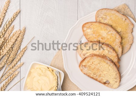 Fresh bread, wheat spike and homemade butter on wooden background. Top view with copy space. - stock photo