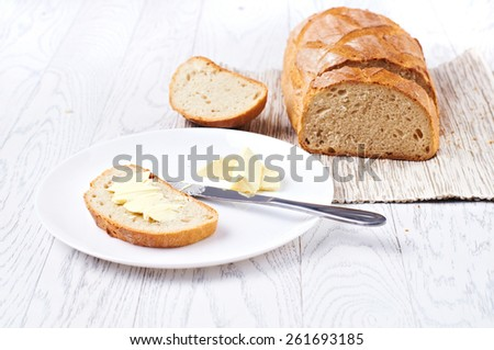 Fresh bread with butter on white table, selective focus - stock photo