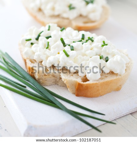 fresh bread with curd and chives - stock photo