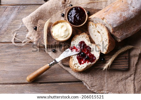 Fresh bread with homemade butter and blackcurrant jam on wooden background - stock photo
