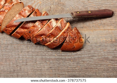 Fresh bread with knife on wooden background - stock photo