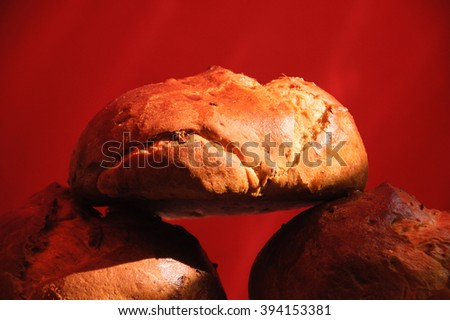 Fresh bread with raisins on red background. - stock photo