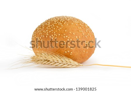 Fresh bread with sesame seeds and spikelets on a white background