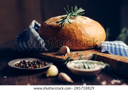 Fresh bread with spices on a dark background, Still life in a rustic style - stock photo
