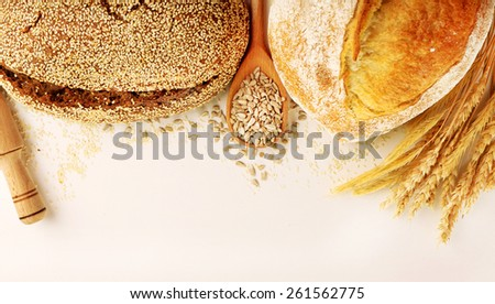 Fresh bread with wheat and wooden spoon of sunflower seeds isolated on white - stock photo