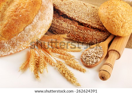 Fresh bread with wheat and wooden spoon of sunflower seeds isolated on white