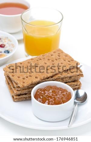 fresh breakfast - crisp bread with jam, orange juice, tea and muesli, vertical - stock photo
