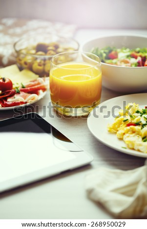 Fresh breakfast food. Scrambled eggs, salad and orange juice. Tablet for Morning News. Concept of healthy business continental breakfast. Image toned, Selective focus, shallow DOF. - stock photo