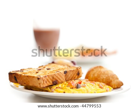 Fresh breakfast - omlette, toast and a croissant with a glass of chocolate milk in the background - stock photo