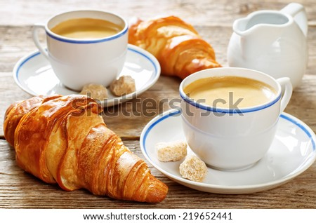 fresh Breakfast with croissants, espresso and milk on a dark wood background. toning. selective focus on the front croissant - stock photo