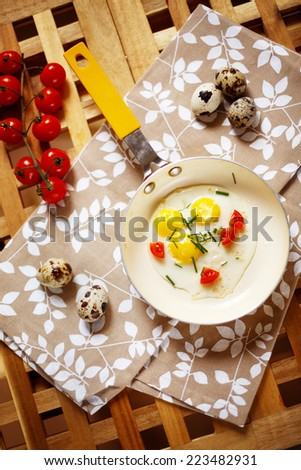 Fresh Breakfast with fried eggs pan. Quail eggs in little yellow frying pan, cherry tomatoes served on wooden table. Top view. - stock photo