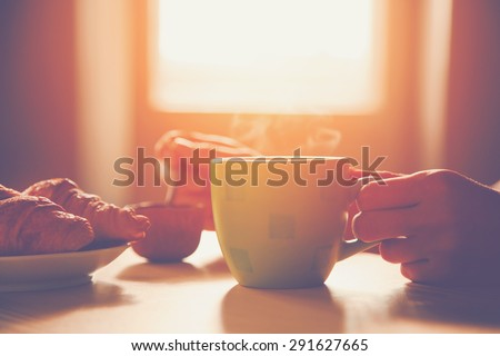 fresh breakfast with hot coffee and croissant in morning sunlight - stock photo