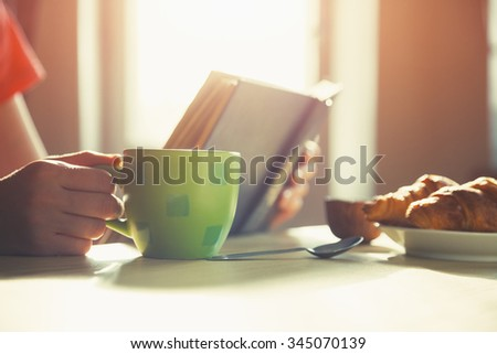 fresh breakfast with hot coffee and reading book in morning sunlight - stock photo