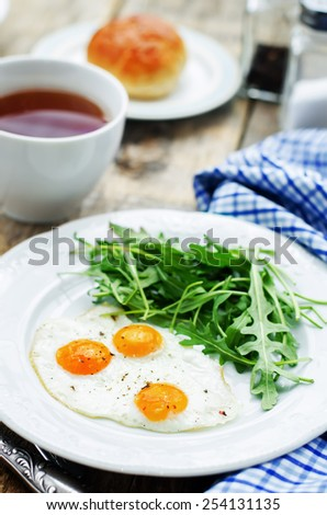 fresh breakfast with scrambled eggs and arugula on a dark wood background. tinting. selective focus - stock photo