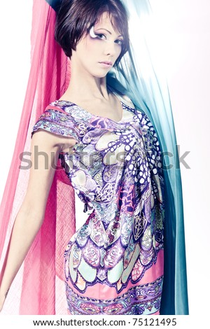 Fresh breeze is waving a piece of silk fabric behind a beautiful young girl - stock photo