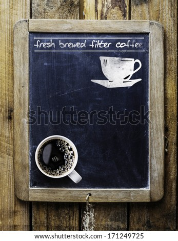 Fresh brewed filter coffee - handwritten on an old vintage school slate used as an advertising sign in a rustic coffee shop with a fresh cup of aromatic coffee in the bottom corner - stock photo