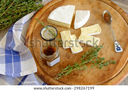 Fresh Brie cheese and a slice on a wooden board - stock photo
