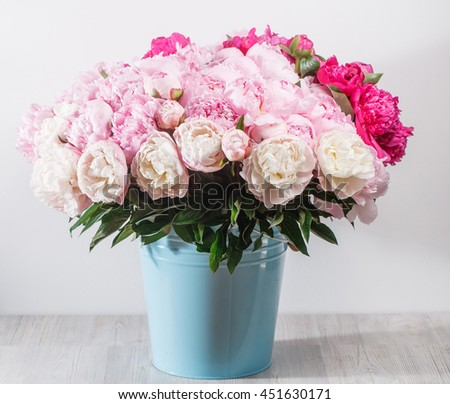 fresh bright blooming peonies flowers with dew drops on petals. white and pink bud. blue bowl bucket - stock photo