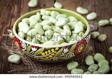 Fresh broad beans in a container on a wooden table. Selective focus. - stock photo