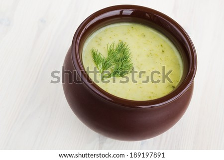 Fresh broccoli cream soup in a clay pot on a table