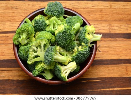 Fresh broccoli in a bowl on wooden cutting board. Preparing food. - stock photo