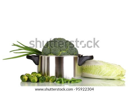 Fresh broccoli in saucepan and cabbages isolated on white