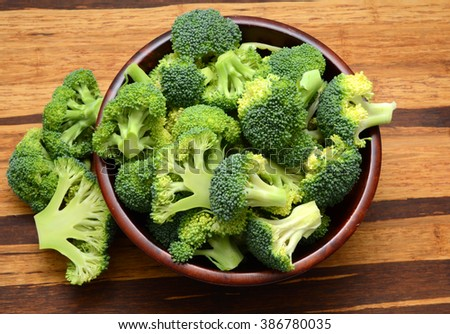 Fresh broccoli on wooden cutting board. Preparing food. - stock photo