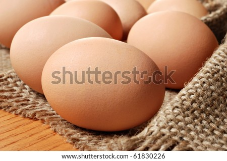 Fresh brown cage free eggs on burlap.  Macro with shallow dof. - stock photo