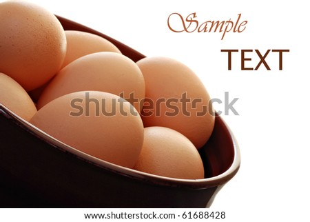 Fresh brown cage free eggs on white background with copy space.  Macro with shallow dof.