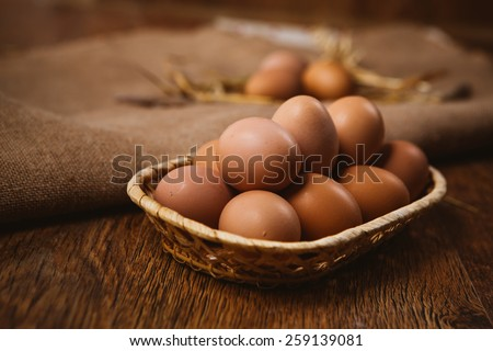 fresh brown eggs and wheat on linen  background - stock photo