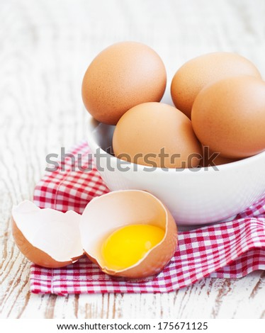 fresh brown eggs in bowl on a wooden background