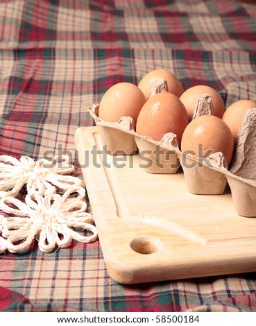 Fresh brown eggs on kitchen table - stock photo
