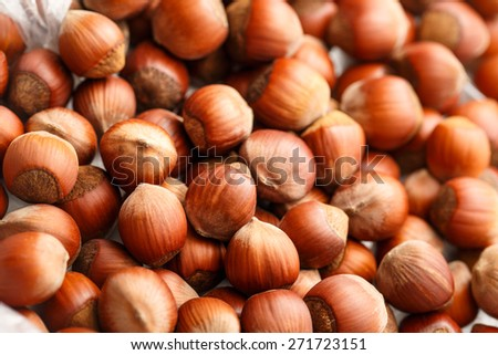 Fresh brown hazelnut as background in closeup - stock photo
