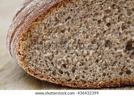 Fresh brown rye bread on a rustic wooden table close up - stock photo