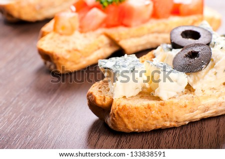 Fresh bruchetta with blue cheese. Selective focus on the blue cheese on bruschetta - stock photo