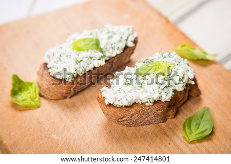 fresh bruschetta with cheese and parsley on wooden plate in studio - stock photo