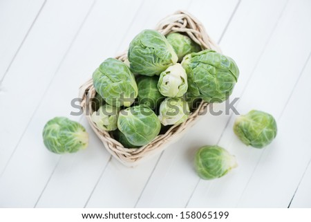 Fresh brussels in a wicker tray on white wooden boards, view from above - stock photo