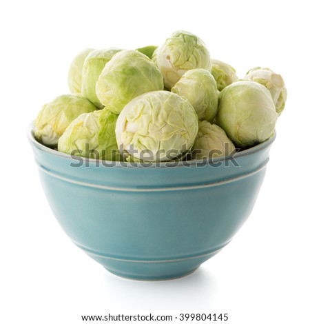 Fresh brussels sprouts on blue ceramic bowl isolated on white background.