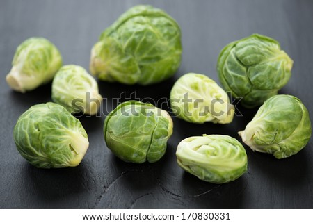 Fresh brussels sprouts over black wooden surface, close-up - stock photo