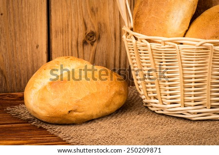 Fresh bun in the basket on the wooden background. - stock photo