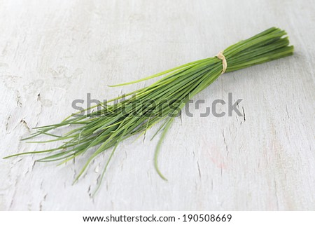 Fresh bunch of chives on grey wooden table - stock photo