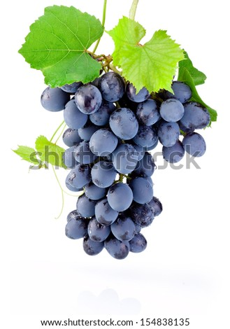 Fresh bunch of grapes with leaves isolated on a white background - stock photo